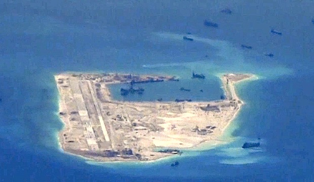 Chinese dredging vessels are purportedly seen in the waters around Fiery Cross Reef in the disputed Spratly Islands in this still image from video taken by a P-8A Poseidon surveillance aircraft provided by the United States Navy on May 21, 2015.